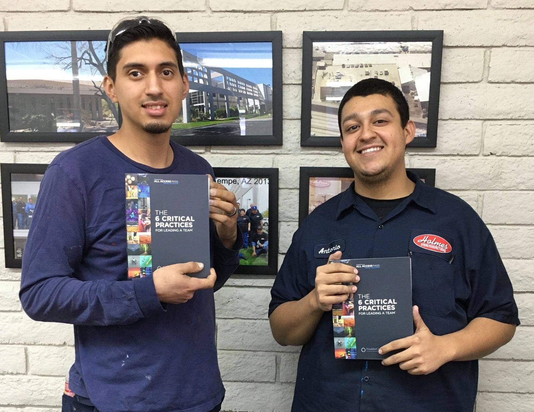 Two employees smiling holding leadership manuals
